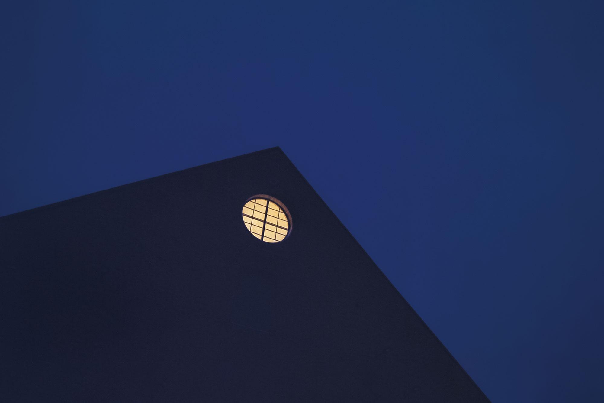 Kalevan Navetan pyöreä ikkuna loistaa illalla